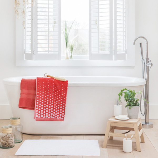 Amara white bathroom with coral Notus bath towels