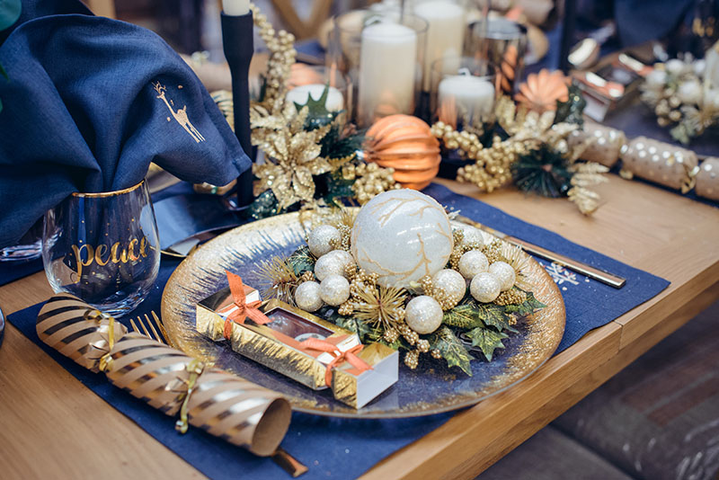 Christmastime table setting, festive dinnerware decorated with details and white balls in Blue and Gold colors. Navy Blue Table Linens and Gold Cutlery. Trends of Winter Holiday Tablescape Decor